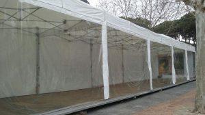 Carpas plegables 3x3 para pasillo con tarima y lonas laterales transparentes.
